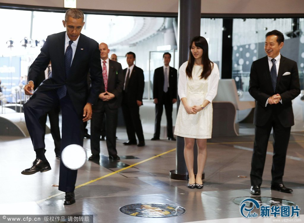 """U.S. President Barack Obama stops a soccer ball kicked by """"Asimo"""" the robot while visiting Miraikan in Tokyo"""